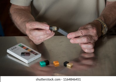 MORGANTOWN, WV - 26 AUGUST 2018: Senior caucasian man putting Juul e-cigarette or nicotine vapor dispenser together with JUULpod