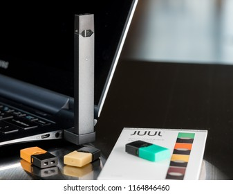 MORGANTOWN, WV - 26 AUGUST 2018: Juul e-cigarette or nicotine vapor dispenser being charged with box and JUULpods on table