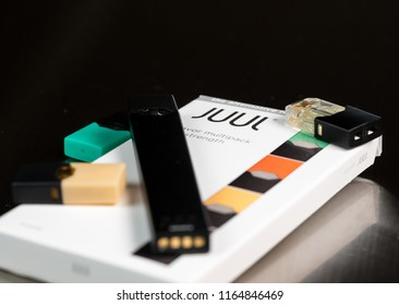 MORGANTOWN, WV - 26 AUGUST 2018: Juul e-cigarette or nicotine vapor dispenser box and JUULpod on dark background