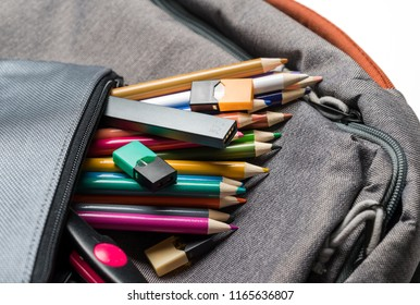MORGANTOWN, WV - 26 AUGUST 2018: Juul e-cigarette or nicotine vapor stick and JUULpods in pencil case on school backpack