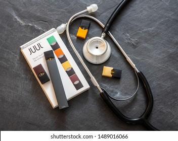 MORGANTOWN, WV - 26 AUGUST 2019: Juul e-cigarette or nicotine vapor dispenser box on slate with stethoscope