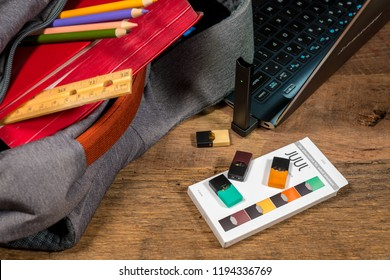 MORGANTOWN, WV - 3 OCTOBER 2018: Juul e-cigarette or nicotine vapor stick and JUULpods charging in laptop by school bag