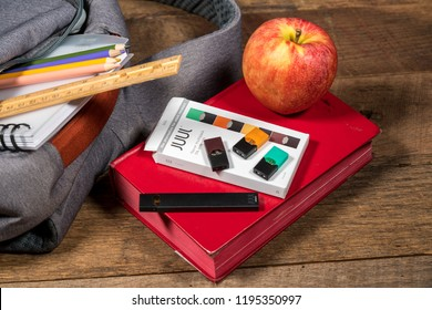 MORGANTOWN, WV - 4 OCTOBER 2018: Juul e-cigarette or nicotine vapor stick and JUULpods charging in laptop by school bag