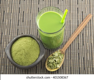 Moringa leaves extract in a glass on wooden background.