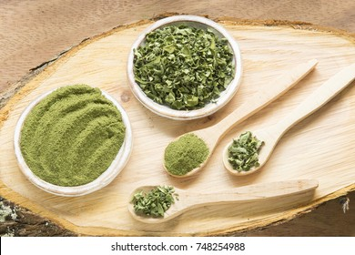 Moringa, leaves and powder on a wooden background- Moringa oleifera