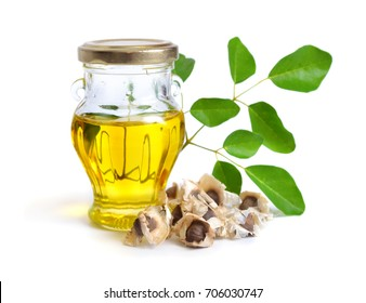 Moringa oleifera oil with seeds and leawes. Isolated on white background.
