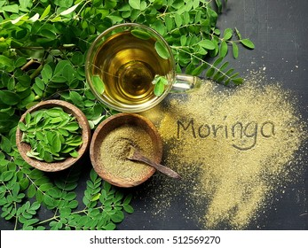 Moringa Oleifera tea with powder on table written moringa wording
