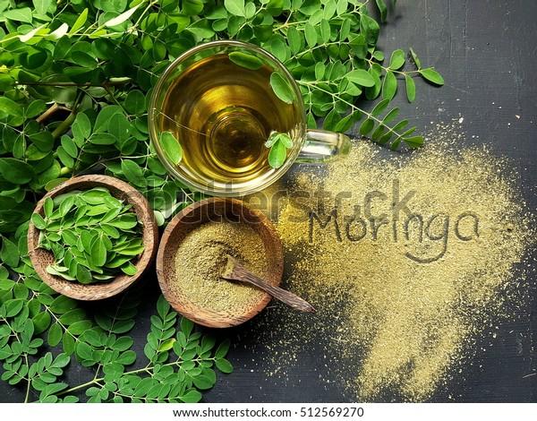 Moringa Oleifera té con polvo sobre la mesa moringa escrito en la redacción