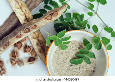 Moringa (Other names are Moringa oleifera Lam., MORINGACEAE, Futaba kom hammer, vegetable hum, Moringa hum bug, Moringa bug Hoo) leaf and seed grinded isolated on white background