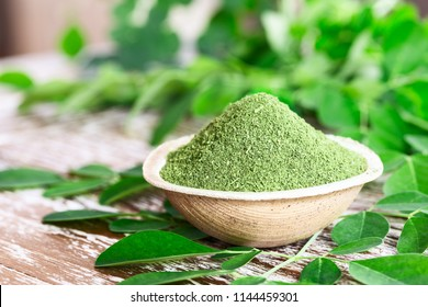 Moringa powder (Moringa Oleifera) in coconut bowl with original fresh Moringa leaves on wooden background. Healthy product, superfood, vitamin.