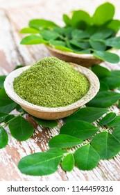 Moringa powder (Moringa Oleifera) in coconut bowl with original fresh Moringa leaves on wooden background. Healthy product, superfood, vitamin, detox.