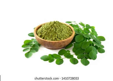 Moringa powder (Moringa Oleifera) in wooden bowl with original fresh Moringa leaves isolated on white background. Healthy product, superfood, vitamin.