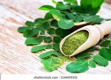 Moringa powder in wooden scoop with original fresh Moringa leaves on wooden table close-up.  Healthy product, superfood, vitamin.