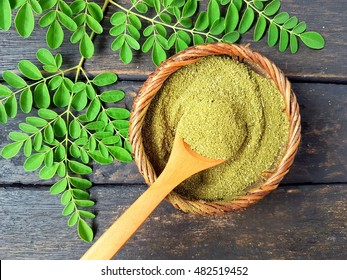 Moringa powder in wooden spoon with moringa fresh leaves