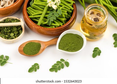Moringa powder,green leaves,oil,seeds and flowers on a white background.