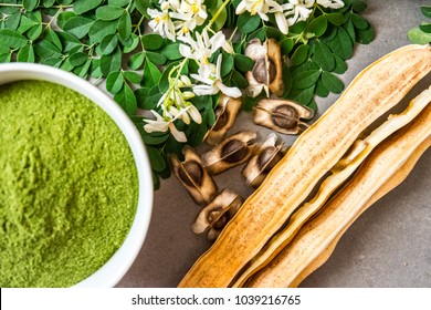 Moringa seeds surrounded by moringa powder ina white bowl moringa leaves and moringa pods