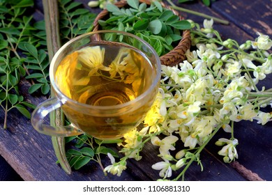 Moringa tea in cup with moringa leaves flowers and seed