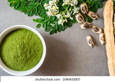 Moringa tea in cup next to moringa seeds and pods, moringa leaves and moringa flowers