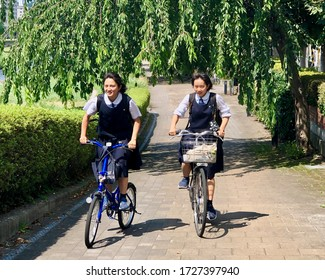 Morioka, Iwate Prefecture, Japan - August 2019 Two school girls ride a bike along a leafy path.