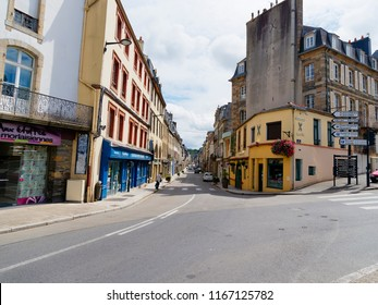 Morlaix, France - August 10 2018: A quite day on the Rue de Paris in Morlaix. A lady with a walking stick makes her way across the road.