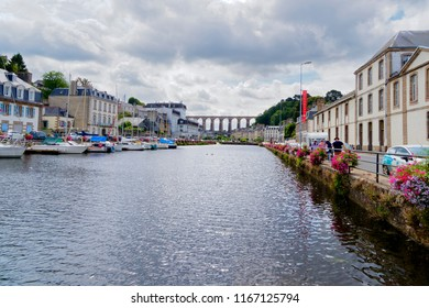 Morlaix, France - August 10 2018: Up the Dussen River, towards Morlaix Viaduct. boats moored on the left, buildings on both banks. A small group of tourists on the right.