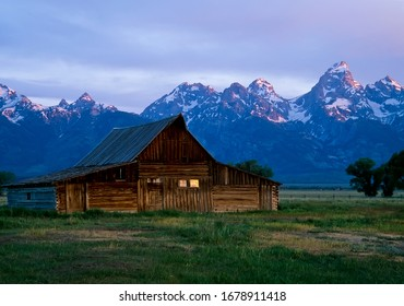 A Mormon barn lit by soft dawn light in front of the Grant Teton Mountains; Grand Teton National Park, Wyoming