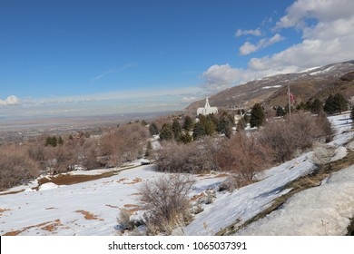 The mormon LDS temple in Bountiful Utah with mountains, blue sky white clouds, Farmington bay in the background and the American flag