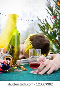 morning after christmas day, woman asleep on table with alcohol at christmas