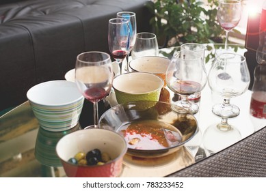 morning after party, dirty dishes, messy table and empty glasses