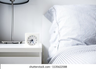 Morning alarm clock in white bedroom interior. Copyspace for text. Minimalist concept