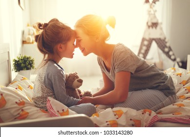 morning awakening. mother wakes her daughter in bed in morning