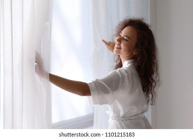 Morning of beautiful African-American woman standing near window