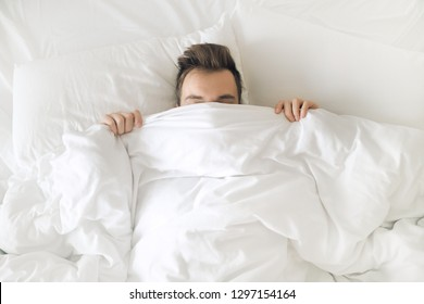 Morning in bed. Man hiding under white blanket in pillows.