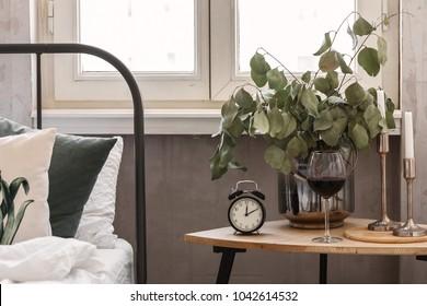 morning. Bedside table. Home decor. Wine glass Clock closeup