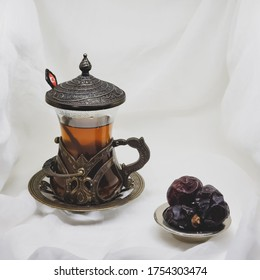 Morning black tea in a glass of distinctive turquoise cup made of chopper and three dates in little plate, white blackground selective focus, foto taken :  Bogor - April  23, 2020