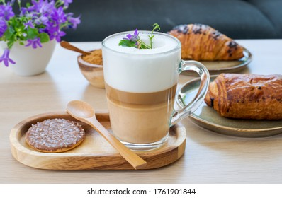 Morning breakfask in the living room, sweet pastry in beautiful plate with a galss of coffee latte macchiato on wooden table with pruple flowers
