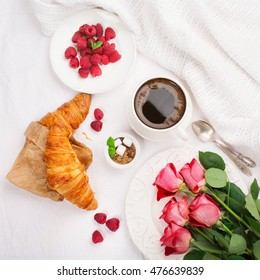 Morning breakfast in bed with cup of coffee, croissants, fresh berries and flowers on wooden tray, top view