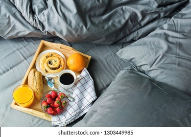 Morning breakfast in bed. Wooden tray coffee bun orange fruit coffee strawberry on grey linens bedding sheet pillow coverlet in gray colors hotel room interior. Copy space