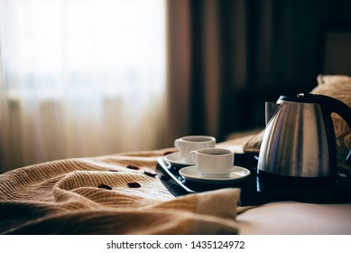 Morning breakfast with black coffee in bedroom. Two cups of coffee on bed decorated with rose petals in luxury hotel bedroom.
