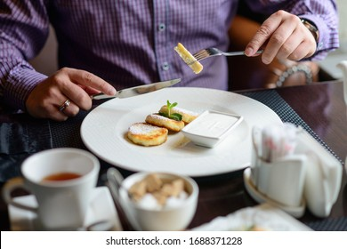 morning Breakfast or brunch in the restaurant. table with drinks and food. man hands cut cheesecakes with a knife and fork. selective focus