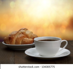 morning breakfast - coffee and croissant in sunrise