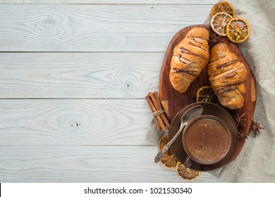 morning breakfast, composition of coffee and croissants on a wooden background