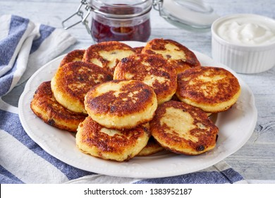 Morning breakfast, cottage cheese fritters with sultanas, raspberry jam and whipped cream on top, served in a white plate, dessert cutlery, on a white wooden table, close up
