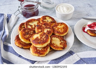 Morning breakfast, farmer cheese fritters with sultanas, raspberry jam and whipped cream on top, served in a white plate, dessert cutlery, on a white wooden table, close up