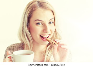 morning, breakfast, food and people concept - happy young woman with cup of tea eating cookie at home