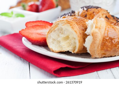 Morning breakfast with fresh croissants yogurt and strawberry on white wooden table