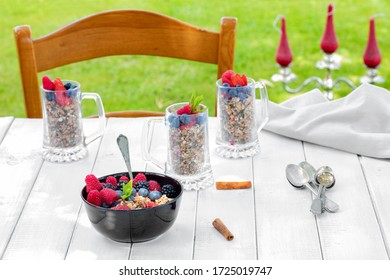 Morning breakfast in the garden with cereals and berries on white table.