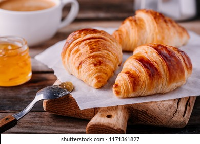 Morning breakfast. Homemade baked croissants with jam and coffee on wooden rustic background
