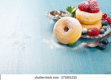 Morning breakfast with mini donuts and berries on plate under powdered sugar on blue wooden background.  Tasty donuts closeup. Doughnut. Copy space.