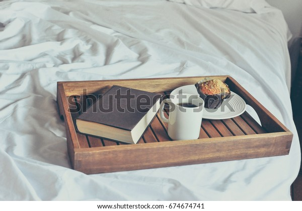 Morning breakfast, mug with coffee, a muffin and a book on a wooden tray on the white bed